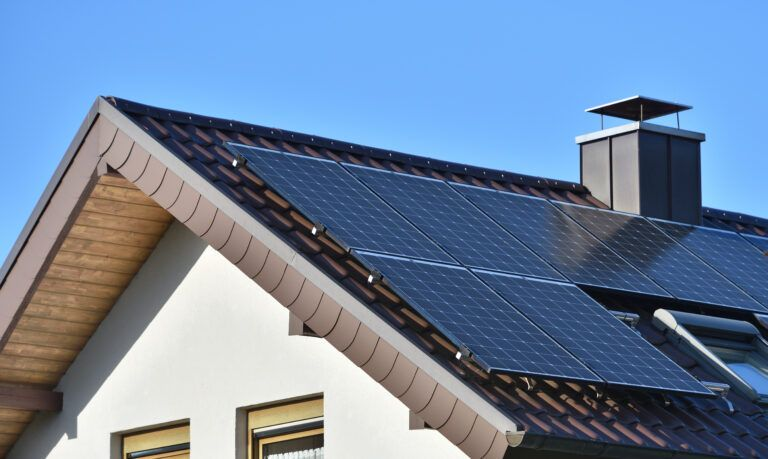 Solar panels installed on the roof of a house with tiles in Europe against the background of a blue sky.